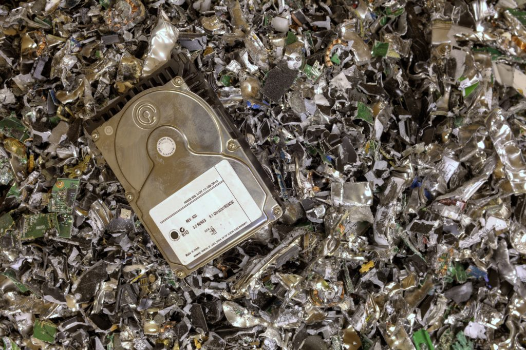 Hard drive resting on a pile of shredded hard drives.